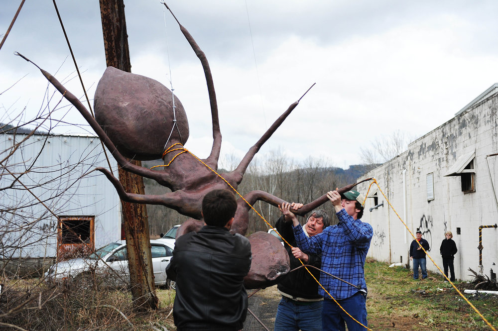 . Tommy Harris, Evan Deacon and Mark Hutzky help lift an ant to the top of a water tower at the abandoned Stillwater plant on Sunday, March 31, 2013, in Goshen, Va. Mark Cline does an April Fools prank every year ó�this year, placing a large ant sculpture on top of the water tower in Goshen, Va. Cline is notorious in the Shenandoah Valley for his annual elaborate sculpture-based pranks, such as Foam Henge.  (AP Photo/The Daily News Leader, Katie Currid)