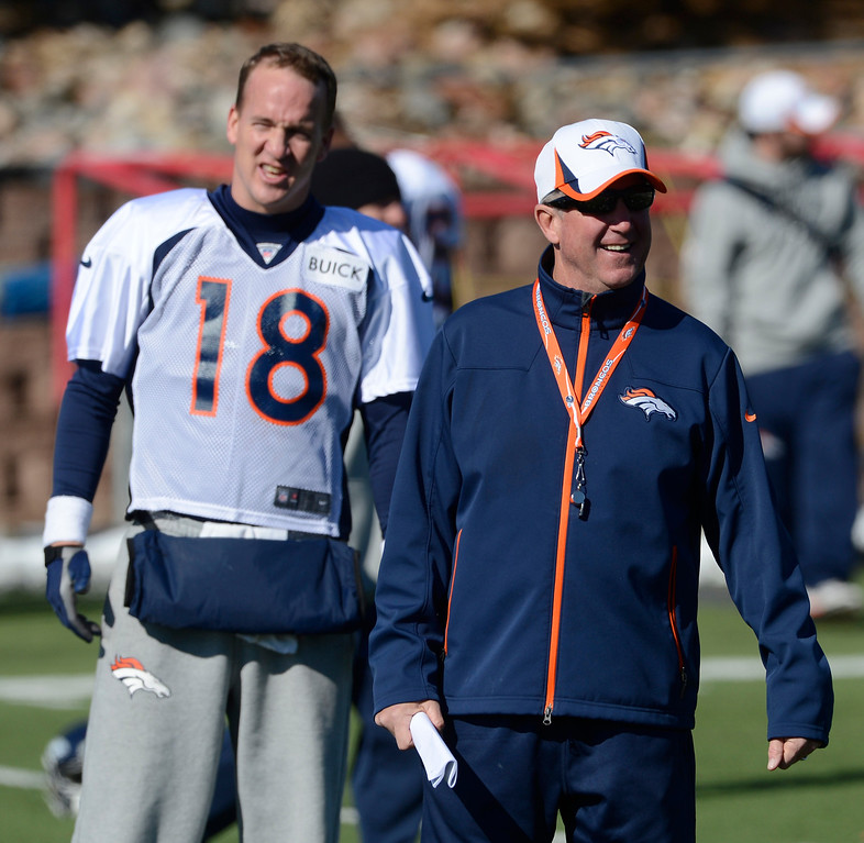 . Denver Broncos head coach, John Fox, right, smiles as his QB, Peyton Manning, left, talks to his during practice Friday morning, October 18, 2103.  (Photo By Andy Cross/The Denver Post)