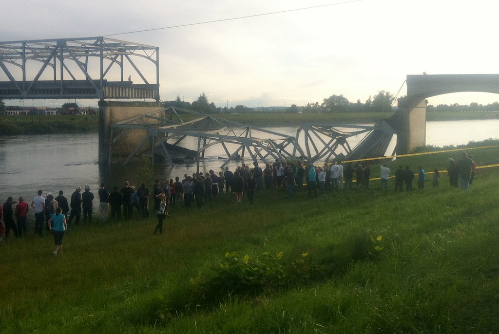 . In this photo provided by NWCN, people look on after the Interstate 5 bridge collapsed over the Skagit River in Skagit County, Wash., Thursday, May 23, 2013. The four-lane bridge over the Skagit River collapsed about 7 p.m., Trooper Mark Francis said. There was no immediate estimate of how many people were in the water or whether there were any injuries or deaths, he said. (AP Photo/NWCN, Selina Dziura)