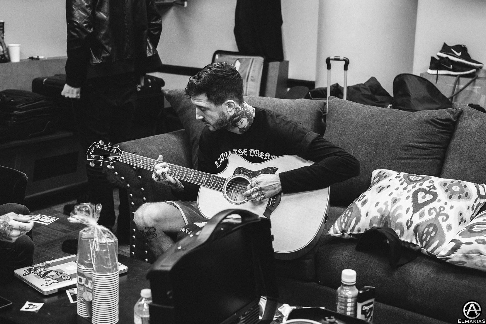 Austin practicing his acoustic guitar backstage