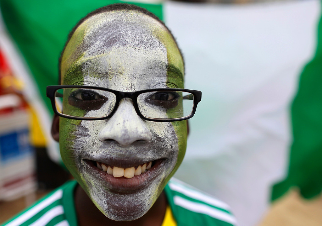 . A young Nigeria soccer fan poses for a picture before his team\'s World Cup round of 16 match against France previous a live telecast inside the FIFA Fan Fest area on Copacabana beach in Rio de Janeiro, Brazil, Monday, June 30, 2014. (AP Photo/Leo Correa)