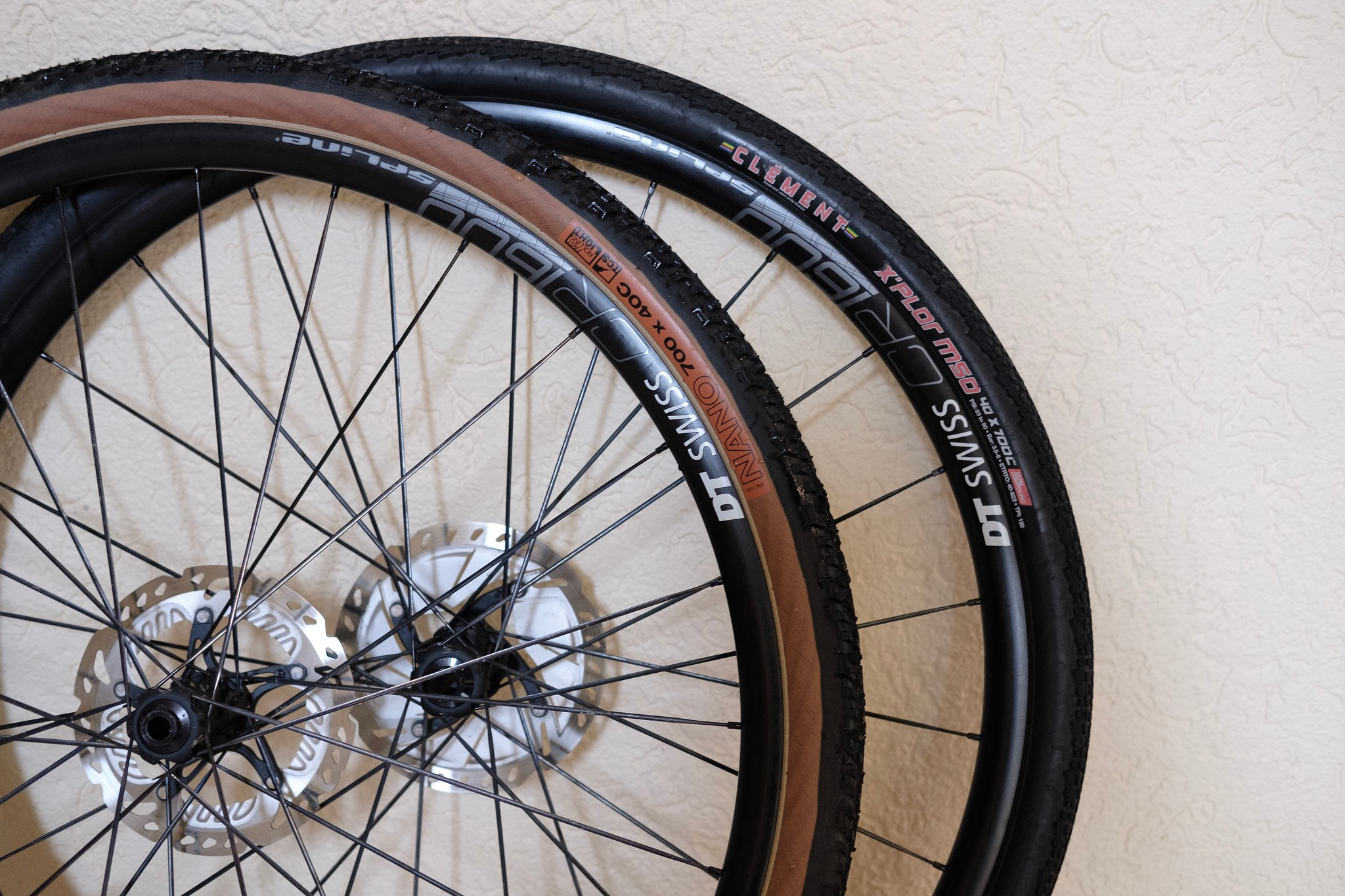 Two DT Swiss CR 1600 Spline 23 wheels with different tyres leaning against a wall