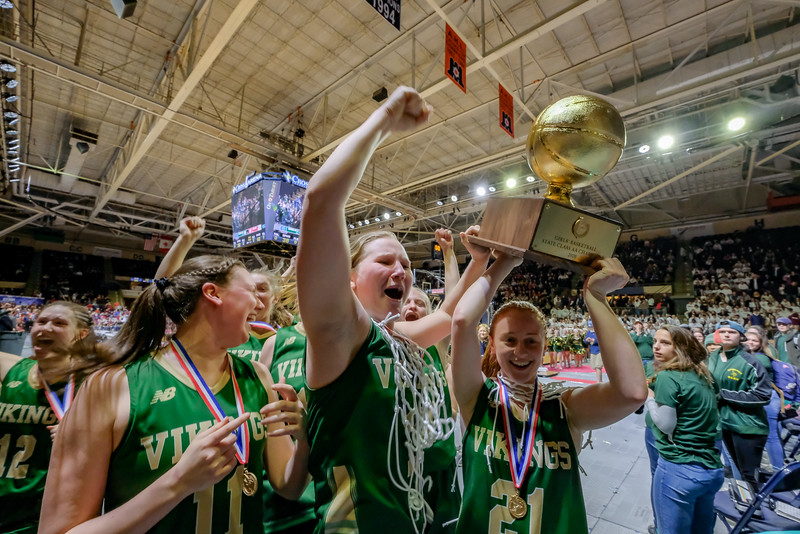 Left to right, Maggie Hartnett, Cecelia Dieterich and Julia Colby bring the Gold Ball over to the Oxford Hills student section.