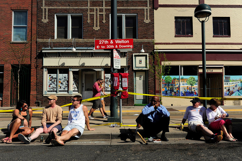 . Festival goers relax on the curb at the Five Points Jazz festival. The event runs 11am to 8pm on May 18, 2013 and is a free community event highlighting local musicians, art and the historic Denver Five Points neighborhood.  (Photo By Mahala Gaylord/The Denver Post)