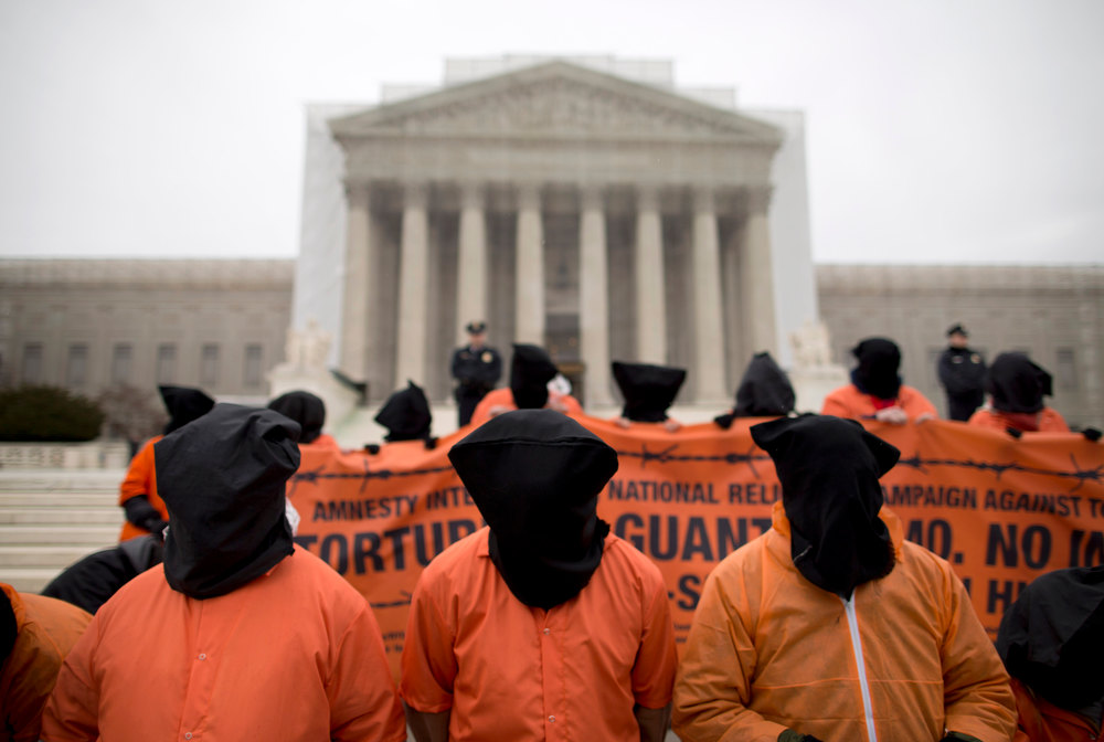 Description of . Demonstrators, dressed as detainees, protest against the U.S. military detention facility in Guantanamo Bay, Cuba, in front of the U.S. Supreme Court in Washington, Friday, Jan. 11, 2013. The protest marks the 11th anniversary of the first detainees being jailed at Guantanamo Bay. (AP Photo/ Evan Vucci)