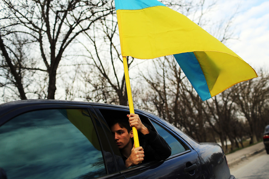 . A pro Ukrainian protester holds a flag near an Ukrainian military base where troops have been locked into the base by the Russians on March 14, 2014 in Bakhchysarai, Ukraine. Hundreds of ethnic Tatars, a Crimean minority with deep roots in the area and who have long suffered under the Russians, held demonstrations throughout Crimea today against the Crimean peninsula becoming part of Russia. As the standoff between the Russian military and Ukrainian forces continues in Ukraine\'s Crimean peninsula, world leaders are pushing for a diplomatic solution to the escalating situation. Crimean citizens will vote in a referendum on 16 March on whether to become part of the Russian federation. (Photo by Spencer Platt/Getty Images)