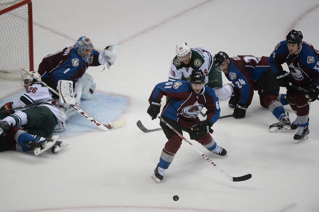 . Andre Benoit (61) of the Colorado Avalanche pulls away with the puck during the second period of action. The Colorado Avalanche hosted the Minnesota Wild in the first round of the Stanley Cup Playoffs at the Pepsi Center in Denver, Colorado on Saturday, April 19, 2014. (Photo by Karl Gehring/The Denver Post)
