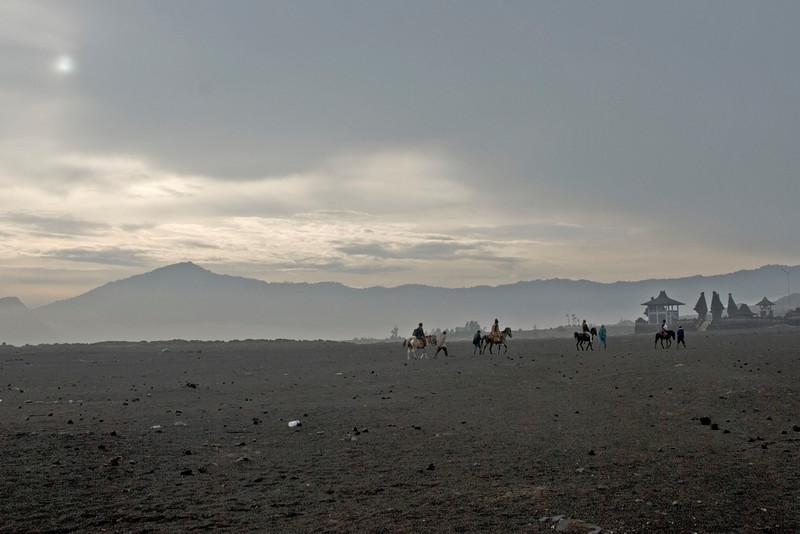 Men riding on horses against hazy skies in MOunt Bromo