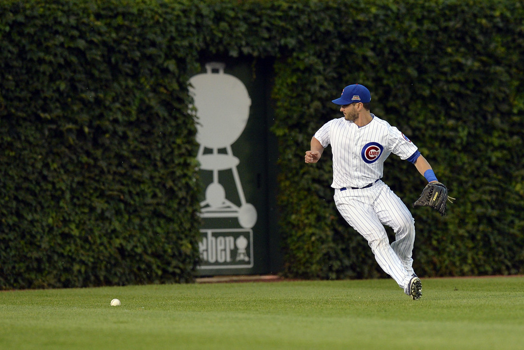 . Left fielder Justin Ruggiano #20 of the Chicago Cubs misplays a a ball off the bat Justin Morneau of the Colorado Rockies that went for a double, and allowing Morneauto advance to third base during the first inning on July 29, 2014 at Wrigley Field in Chicago, Illinois.  (Photo by Brian Kersey/Getty Images)