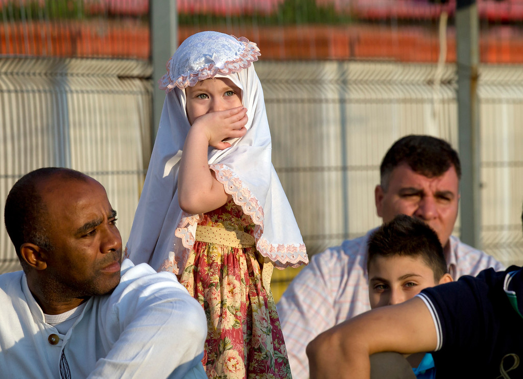 . Sara, 4 years-old reacts before Eid al-Fitr prayers in Bucharest, Romania, Thursday, Aug. 8, 2013. Muslim men and women joined prayers at the Dinamo stadium in the Romanian capital, in the largest Muslim public gathering of the year. Eid al-Fitr marks the end of the holy month of Ramadan, during which Muslims all over the world fast from sunrise to sunset. (AP Photo/Vadim Ghirda)
