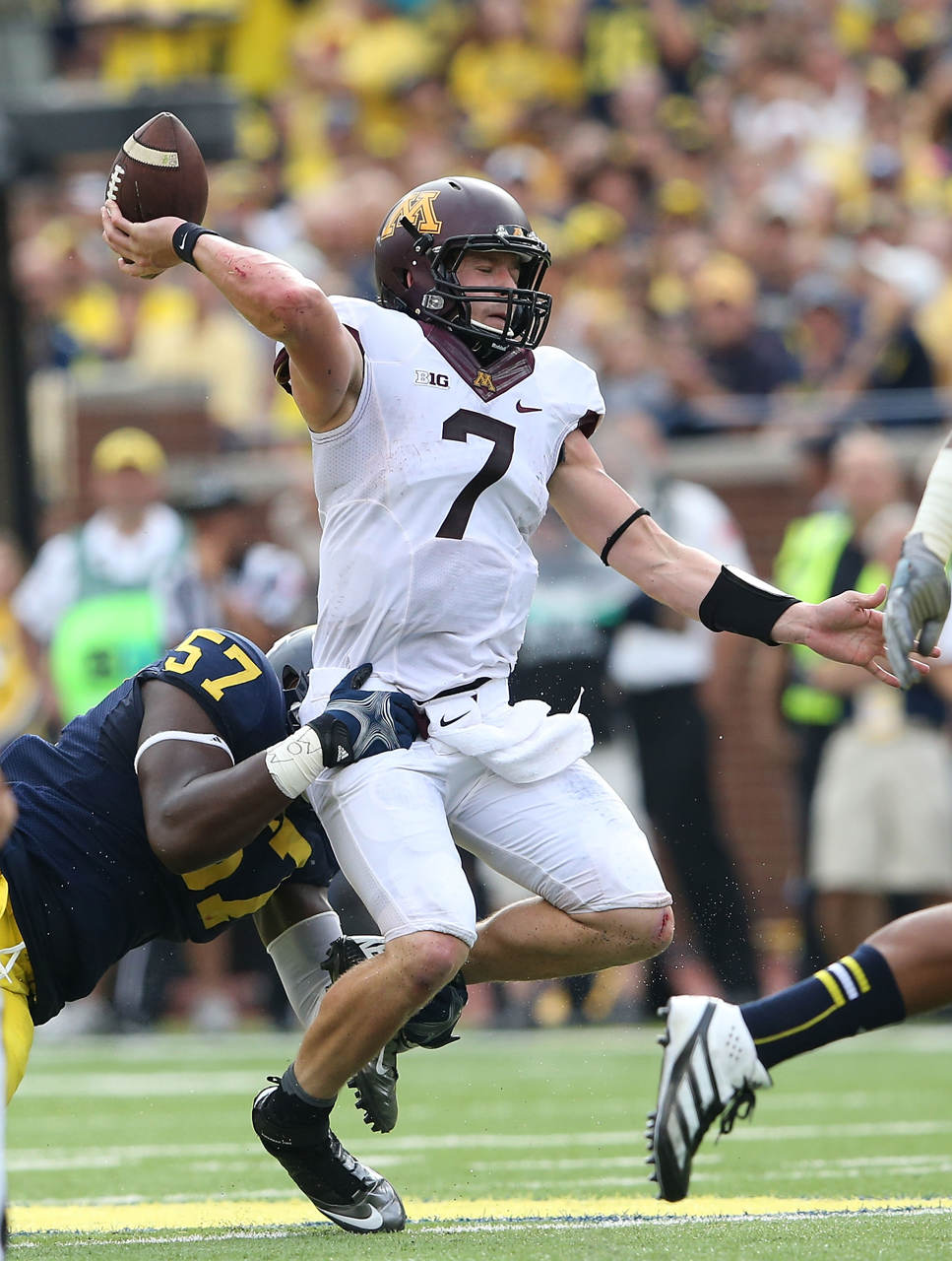 . Minnesota quarterback Mitch Leidner makes a throw as Michigan linebacker Frank Clark attempts to make the stop during the first quarter. (Photo by Leon Halip/Getty Images)