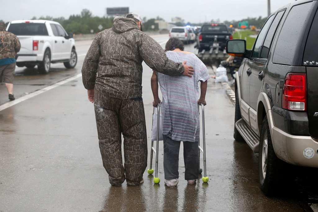 . Volunteer Kyle Denison assist Rosemarie Carpenter after she was rescued by boat during flooding from Tropical Storm Harvey in Orange, Texas, Wednesday, Aug. 30, 2017. (AP Photo/Gerald Herbert)