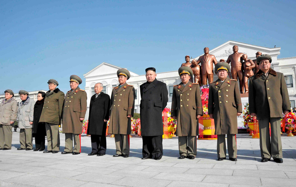Description of . North Korean leader Kim Jong-Un (4th R) and officials attend a wreath laying ceremony in front of a statue of North's founder Kim Il-Sung and his son and late leader Kim Jong-Il at the Mangyongdae Revolutionary School in Pyongyang on the occasion of birth anniversary of the late leader Kim Jong-Il, which falls on Saturday, in this undated recent picture released by the North's official KCNA news agency on February 16, 2013. REUTERS/KCNA