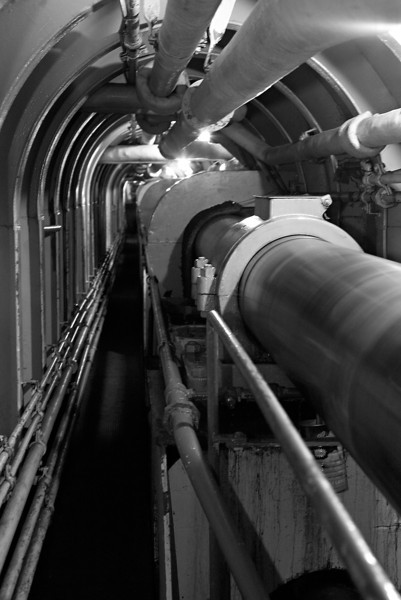 A narrow catwalk runs alongside the propeller shaft for over a hundred feet from the engine room to the stern.  The spinning shaft is at least a foot in diameter.  In the foreground is one of the bearings that support the shaft.  Behind that is a fixed shield which covers one of the bolted joints in the shaft.