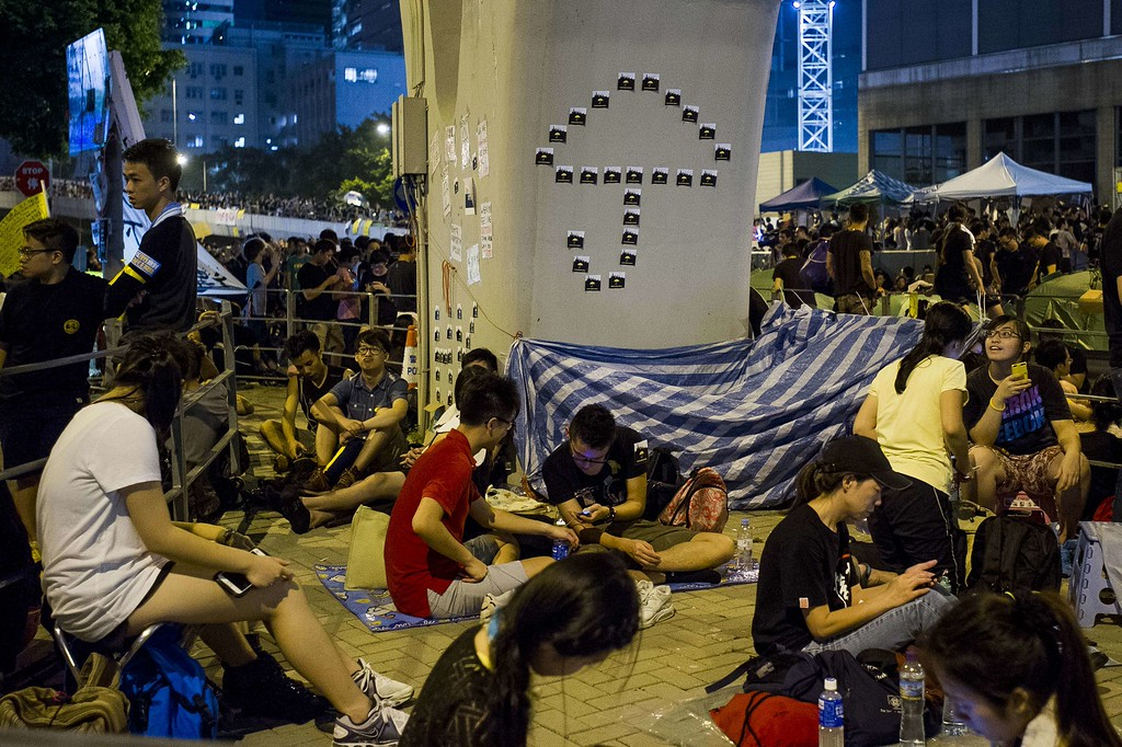. Pro-democracy protestors sit next to a pillar decorated with an umbrella in the Admiralty district of Hong Kong on October 1, 2014.   Hong Kong has been plunged into the worst political crisis since its 1997 handover as pro-democracy activists take over the streets following China\'s refusal to grant citizens full universal suffrage. XAUME OLLEROS/AFP/Getty Images