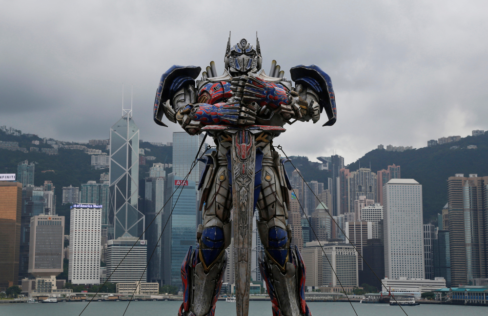 ". A giant figure of Optimus Prime from the movie ""Transformers 4: Age of Extinction\"" is displayed for the film\'s world premiere in Hong Kong Thursday, June 19, 2014. The latest installment in the blockbuster series of \""Transformers\"" films is making its world premier not in the usual entertainment hubs of Los Angeles or New York but in the wealthy Chinese metropolis of Hong Kong, the latest sign of Hollywood\'s increasing focus on China\'s booming film market. (AP Photo/Kin Cheung)"