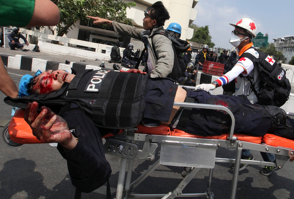 . A bomb injured Thai riot police officer is carried to a hospital after a grenade attack during clashes with anti-government protesters at a protest site near Democracy Monument in Bangkok, Thailand, 18 February 2014.   EPA/PETER CHAN