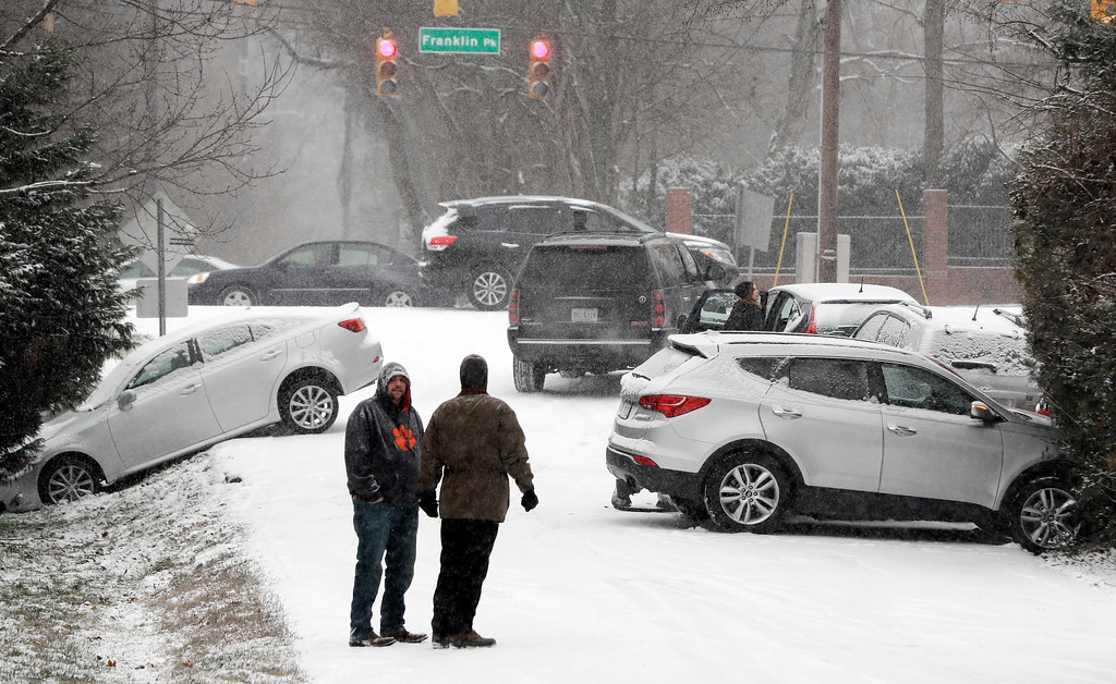 . Motorists talk outside their cars after being involved in several accidents due to icy roads, Friday, Jan. 6, 2017, in Nashville, Tenn. Winter weather closed schools and made driving conditions hazardous. (AP Photo/Mark Humphrey)