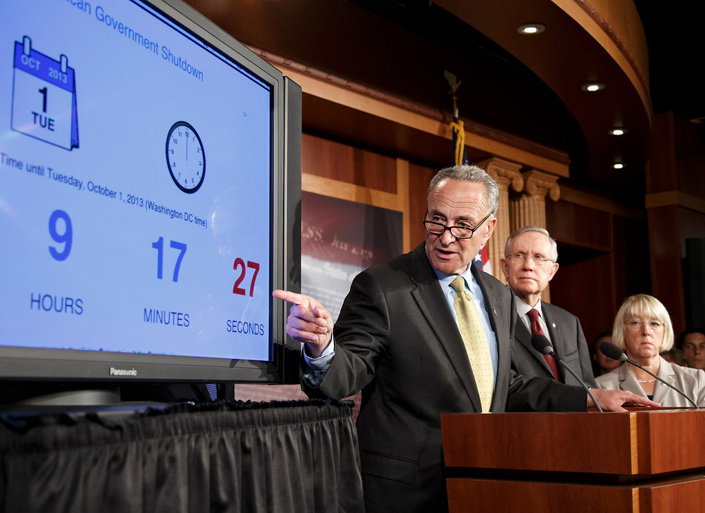 . Sen. Charles Schumer, D-N.Y., left, accompanied by Senate Majority Leader Harry Reid of Nev., center, and Senate Senate Budget Committee Chair Sen. Patty Murray, D-Wash., points to a countdown clock during a news conference on Capitol Hill in Washington, Monday, Sept. 30, 2013, after the Democratic-led Senate rejected conditions that House Republicans attached to a temporary spending bill. On the brink of a government shutdown, the Senate voted 54-46 on Monday to strip a one-year delay in President Barack Obama\'s health care law from the bill that would keep the government operating.  (AP Photo/J. Scott Applewhite)