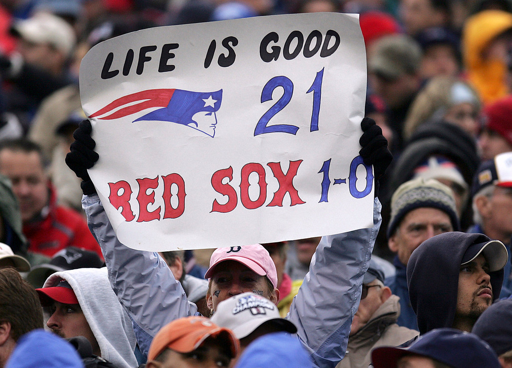 . A New England Patriots fan holds up a sign, Sunday, Oct. 24, 2004, in Foxboro, Mass., for the Patriots\' record number of consecutive wins and the Boston Red Sox win against the St. Louis Cardinals in game one of the World Series on Saturday. The Patriots won in Foxboro against the New York Jets, 13-7. (AP Photo/Michael Dwyer)