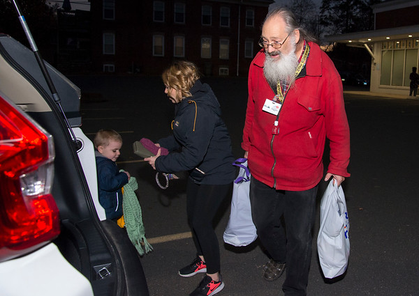 11/25/19 Wesley Bunnell | StaffrrThanksgiving meals were handed out by HRA Bristol on Monday evening by workers and volunteers. Driver Michael Bachand helps carry bags of food out for a client.