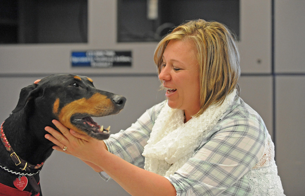 ". Shawn Hricak from Minneapolis couldn\'t wait to get home to her three dogs. Here she pets ""Jackie\"", a Doberman Pinscher. New program at LAX called PUP (Pets Unstressing People) uses certified dogs to walk the terminals with their volunteer owners to greet passengers and help ease the tensions of modern airline traveling.   Photo by Brad Graverson 4-11-13"