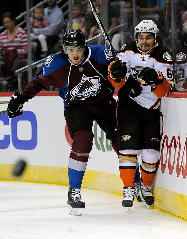 . Colorado Avalanche right wing Dennis Everberg, left, checks Anaheim Ducks defenseman Kevin Gagne, right, in the first period of an NHL preseason hockey game Monday, Sept. 22, 2014 in Denver. (AP Photo/Chris Schneider)