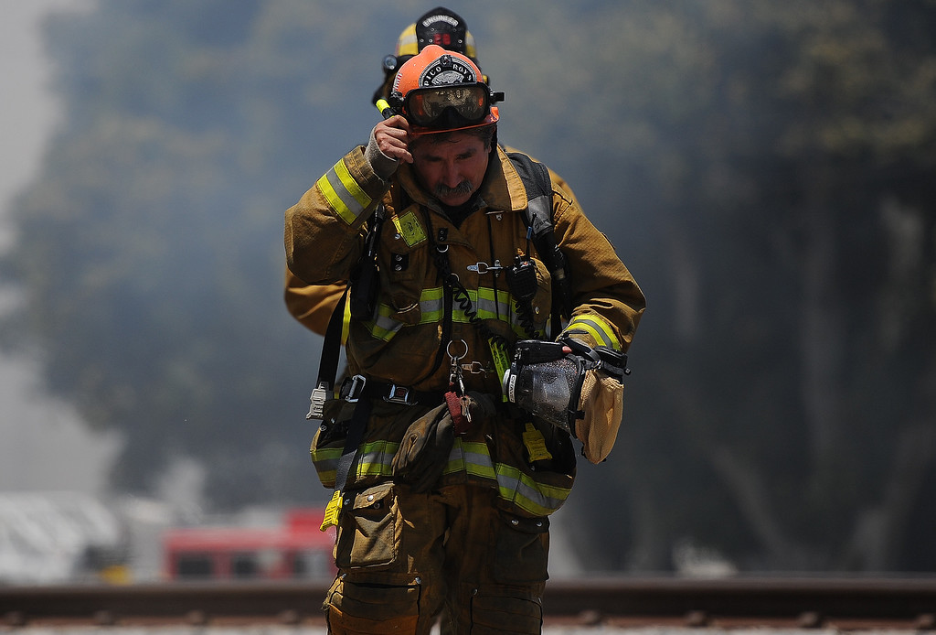 . Los Angeles County firefighter capt. takes a break after battling a 3-alarm fire at an abandoned warehouse near 9th Avenue and Clark Avenue on Tuesday, July 9, 2013 in City of Industry, Calif.  (Keith Birmingham/Pasadena Star-News)