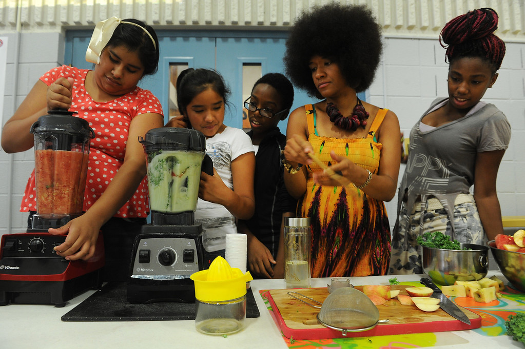". DENVER, CO - JULY 1:  Neambe Leadon Vita, second from right, helps summer camp students make juice from fresh local produce that includes cucumbers, strawberries, limes, watermelon, apples, coconut water and baby kale during a summer camp at St. Charles Recreation Center at 3777 Lafayette Street in Denver, CO. on July 1, 2013.  The kids are from left to right:  Kelly Garcia, 9, Caren Alvarado, 12, Dashawn Tolbert, 13, and Letencia Blake, 14, far right.   DJ Cavem Moetavation, not shown, and his wife Neambe Leadon Vita hold the camp to introduce kids to healthy eating habits, teach them about organic farming and changing the way they think about food. They also make organic juice during the day using produce from the couple\'s garden which includes cucumbers, strawberries, watermelon, kale, lime and coconut water.   As part of our ""Summer of Love\"" series for the Style section we profile the relationship of DJ Cavem Moetavation (a.k.a. Ietef Vita) and his wife Neambe Vita.  They are proud and longtime Five Points residents. They\'re artists, community activists, musicians, teachers and more.  They espouse the idea of being vegan or vegetarian and promote eating healthfully and organically.  (Photo by Helen H. Richardson/The Denver Post)"