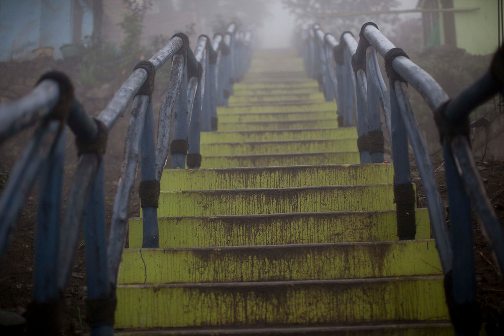 ". In this July 24, 2013 photo, the fog covered stairs leading up to the Bella Vista del Paraiso neighborhood are seen in Lima, Peru. For roughly four months a year, the sun abandons Peru\'s seaside desert capital, suffocating it under a ponderous gray cloudbank and fog that coats the city with nighttime drizzles. The cold Humboldt current that runs north from Antarctica along the coast is the culprit, colliding with the warmer tropical atmosphere to create the blinding mists called ""garua\"" in coastal Chile and Peru. (AP Photo/Rodrigo Abd)"
