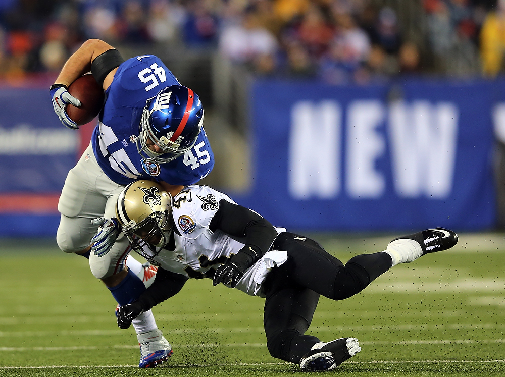 Description of . Roman Harper #41 of the New Orleans Saints knocks over  Henry Hynoski #45 of the New York Giants on December 9, 2012 at MetLife Stadium in East Rutherford, New Jersey.  (Photo by Elsa/Getty Images)