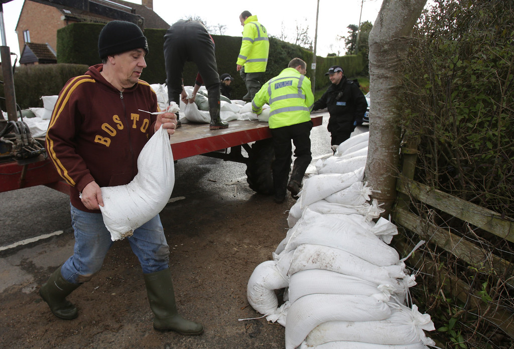 . People unload sandbags from a tractor trailer in the village of East Lyng along the flooded A361 on February 13, 2014 in Somerset, England.  (Photo by Matt Cardy/Getty Images)