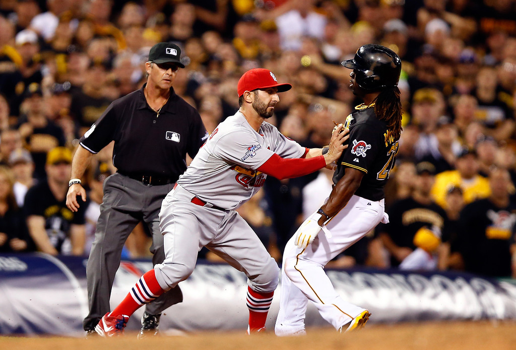 . Daniel Descalso #33 of the St. Louis Cardinals tags Andrew McCutchen #22 of the Pittsburgh Pirates at third base during Game Three of the National League Division Series at PNC Park on October 6, 2013 in Pittsburgh, Pennsylvania.  (Photo by Justin K. Aller/Getty Images)