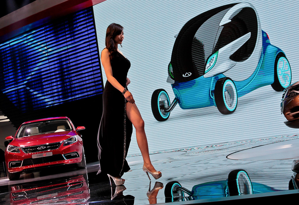 . A model walks past Alpha 7 car, left, and @ANT2.0 concept car shown on the screen, made by Chinese automaker Chery on display at the Shanghai International Automobile Industry Exhibition (AUTO Shanghai) media day in Shanghai Saturday, April 20, 2013. (AP Photo)