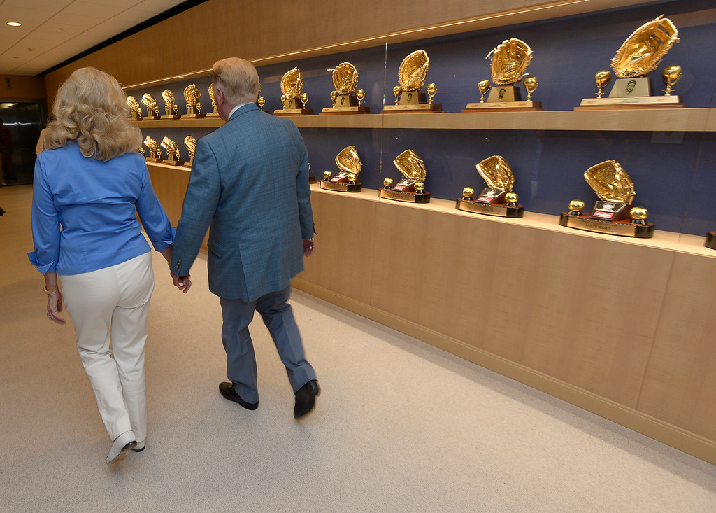. Vin Scully and his wife Sandy Scully walk down the hall, passing several Golden Glove awards, after holding a press conference at Dodger Stadium. Scully, a Hall of Fame broadcaster, will return to the Dodger broadcast booth for an unprecedented 66th season in 2015. The announcement was made by several Dodger players on Dodger Vision during last night�s game against the Atlanta Braves. Los Angeles, CA. 7/30/2014(Photo by John McCoy Daily News)