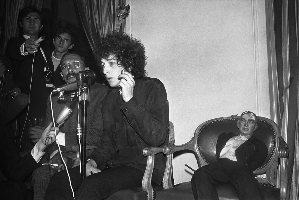 . American folk singer Bob Dylan smokes as he faces the media during a press conference at the Hotel George V in Paris, France on May 23, 1966. He will appear on Tuesday at the Paris Olympia music hall. Beside him is a puppet. (AP Photo/Pierre Godot)