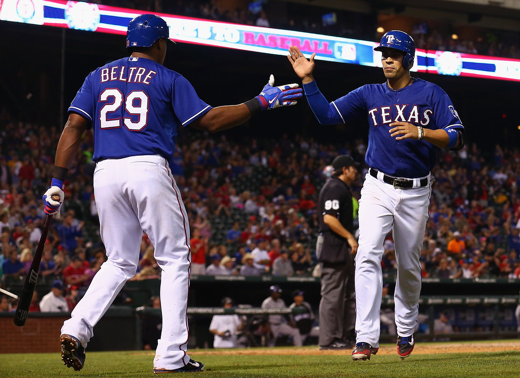 . ARLINGTON, TX - MAY 08:  Adrian Beltre #29 of the Texas Rangers celebrates with Robinson Chirinos #61 of the Texas Rangers after Chirinos scored against the Colorado Rockies in the bottom of the seventh inning at Globe Life Park in Arlington on May 8, 2014 in Arlington, Texas.  (Photo by Tom Pennington/Getty Images)