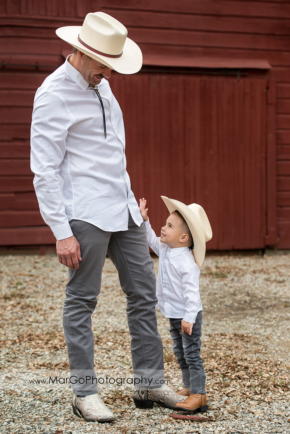 man and little boy in white shirts, gray jeans and cowboy hats on the red wooden barn in Shinn Historical Park and Arboretum in Fremont