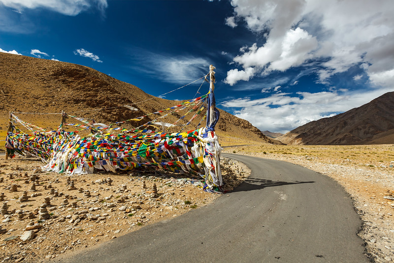 Road and Buddhist prayer flags (lungta) at Namshang La pass. Ladakh, India