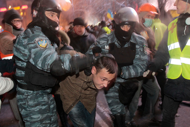. Ukrainian riot policemen pull a Pro-European Union activist out form a tent camps on the Independence Square in Kiev, Ukraine, Wednesday, Dec. 11, 2013. Security forces clashed with protesters as they began tearing down opposition barricades and tents set up in the center of the Ukrainian capital early Wednesday, in an escalation of the weeks-long standoff threatening the leadership of President Viktor Yanukovych. (AP Photo/Sergei Chuzavkov)