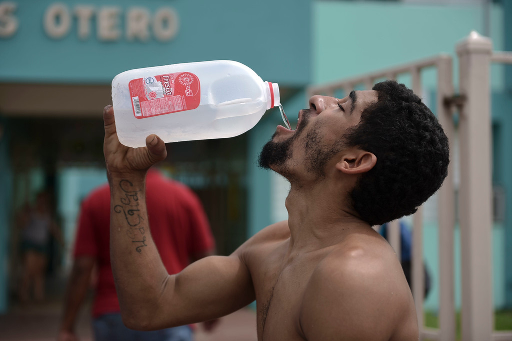 . Julio Ortiz Montanez drinks water at the Jose Robles Otero Elementary School after the passing of Hurricane Maria, in Toa Baja, Puerto Rico, Friday, September 22, 2017. Because of the heavy rains brought by Maria, thousands of people were evacuated from Toa Baja after the municipal government opened the gates of the Rio La Plata Dam. (AP Photo/Carlos Giusti)