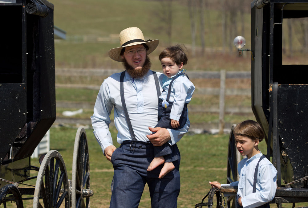 . Freeman Burkholder carries his son to the school house for the end of the school year celebration in Bergholz, Ohio on Tuesday, April 9, 2013.  Burkholder is one of the Amish members convicted in a beard and hair cutting scandal against other Amish people.  (AP/Scott R. Galvin)