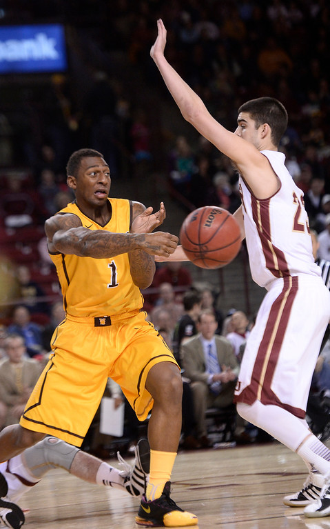 . Wyoming Cowboys guard Charles Hankerson Jr. (1) makes a pass around Denver Pioneers guard Brett Olson (23) during the first half December 15, 2013 Magness Arena. (Photo by John Leyba/The Denver Post)