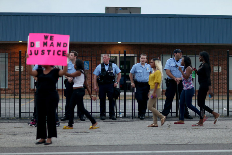 """. A demonstrator holds a sign reading, \""""We Demand Justice\"""", in front of a line of police as demonstrators continue to make their voices heard in the shooting death of Michael Brown on August 17, 2014 in Ferguson, Missouri. Violent outbreaks have taken place in Ferguson since the shooting death of Michael Brown by a Ferguson police officer on August 9th.  (Photo by Joe Raedle/Getty Images)"""