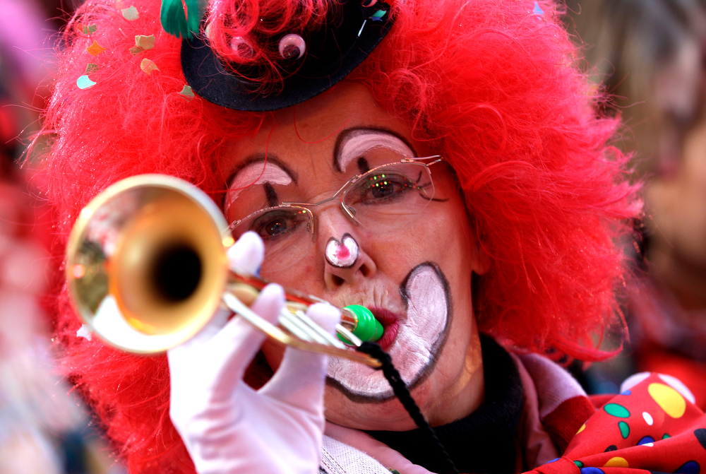 """Description of . A carnival  reveller dressed as a clown celebrates the start of the street-carnival with its tradition of fools entering the town halls and women cutting off men\'s ties with scissors on carnival\'s so called \""""Old Women\'s Day\"""" in Cologne, Germany, Thursday, Feb. 7, 2013. The \""""Old Women\'s  Day\""""  is traditionally the beginning of  street carnival, the foolish street spectacles in the carnival centers of Duesseldorf, Mainz and Cologne. (AP Photo/Frank Augstein)"""
