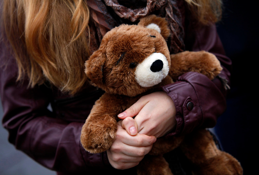 . A woman carries a teddy bear to a makeshift memorial in Newtown, Connecticut December 17, 2012. Twelve girls, eight boys and six adult women were killed in a shooting on Friday at Sandy Hook Elementary School in Newtown. REUTERS/Joshua Lott