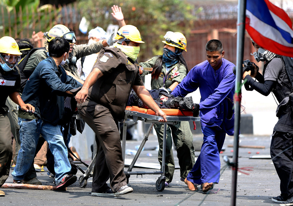 . An injured Thai policeman is helped on a stretcher by medic officials and protesters after an explosion during a clash between policemen and anti-government protesters Tuesday, Feb. 18, 2014 in Bangkok, Thailand.   (AP Photo/Apichart Weerawong)