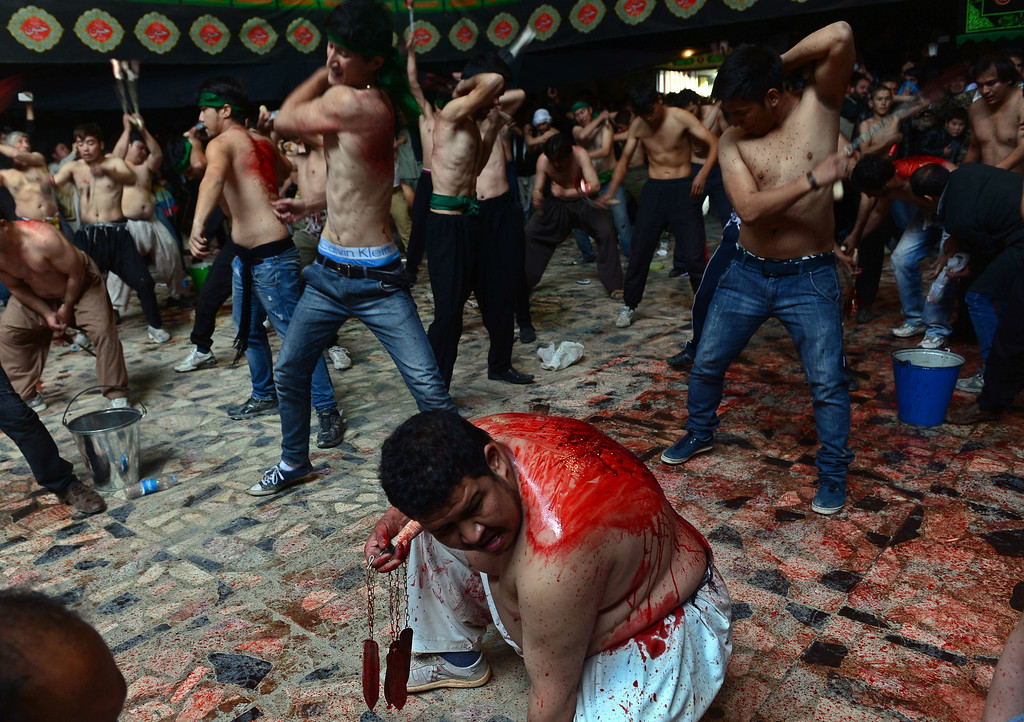 . In this photograph taken on October 31, 2014 Afghan Shiite Muslim devotees beat themselves with chains and blades as part of a self-flagellation ritual during Ashura commemorations at a mosque in Kabul on October 31, 2014. WAKIL KOHSAR/AFP/Getty Images