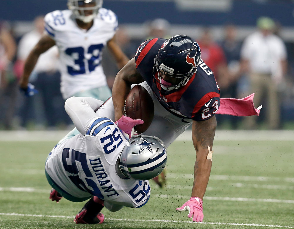 . Dallas Cowboys outside linebacker Justin Durant (52) tackles Houston Texans running back Arian Foster (23) during the first half of an NFL football game, Sunday, Oct. 5, 2014, in Arlington, Texas. (AP Photo/Brandon Wade)