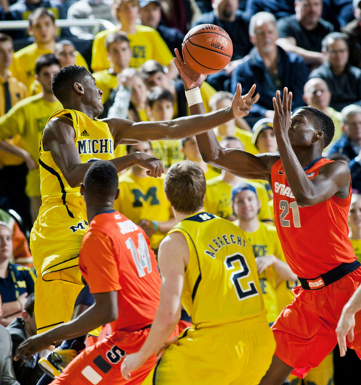 . Michigan guard Caris LeVert, top left, battle for a loose ball with Syracuse forward Tyler Roberson (21), as Syracuse guard Kaleb Joseph (14) and Michigan guard Spike Albrecht (2) watch, in the first half of an NCAA college basketball game at Crisler Center in Ann Arbor, Mich., Tuesday, Dec. 2, 2014. (AP Photo/Tony Ding)